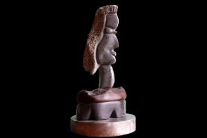 """Rhonda Contemplating the Options"". Springstone, wood, w/ metal base. 12"" T x 6"" W. Private collection. © 2007 Ellza Coyle."